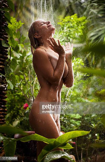 Seductive woman enjoying in tropical shower.