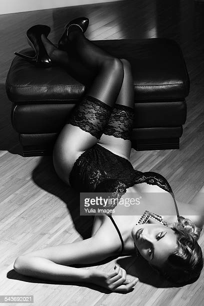 seductive woman in lingerie lying on the floor - black women in stockings stock photos and pictures