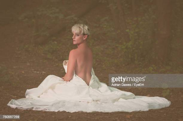 Seductive Woman In Wedding Dress Sitting On Field At Forest