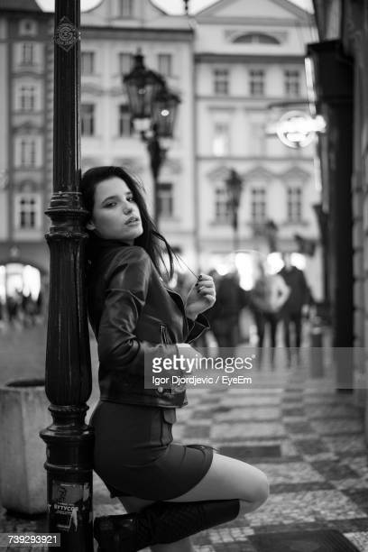 seductive woman leaning on street light at sidewalk in city - seductive women stock pictures, royalty-free photos & images