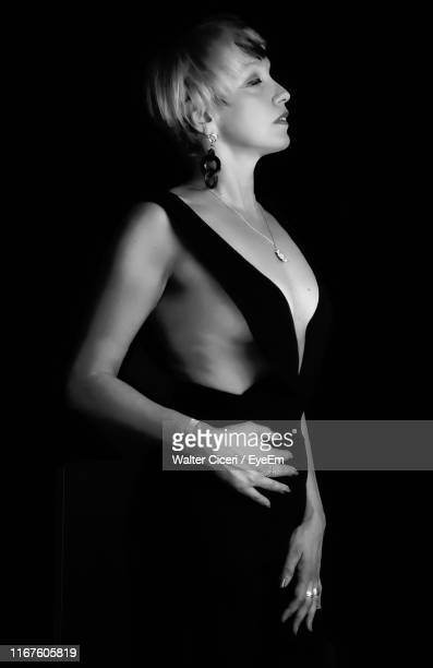 seductive woman standing against black background - walter ciceri foto e immagini stock