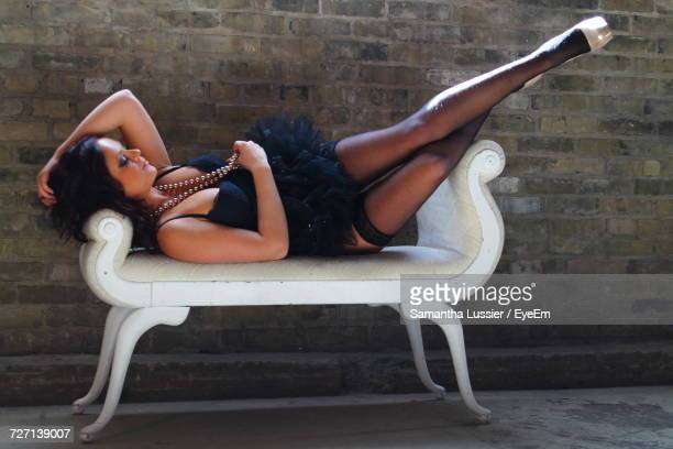 seductive woman wearing black tutu lying on couch against wall in boudoir - black dress with stockings foto e immagini stock
