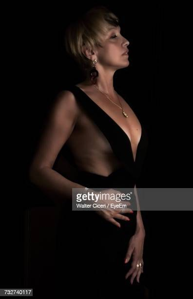 seductive woman with eyes closed standing against black background - walter ciceri foto e immagini stock