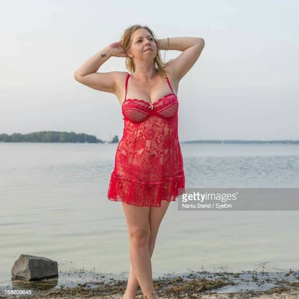 seductive women with hands behind head wearing nightie while standing at beach against clear sky - women in slips stock photos and pictures