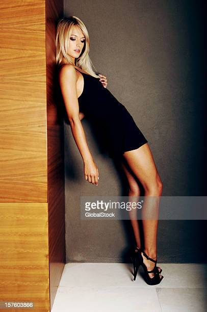 seductive young woman posing in black dress - skinny black woman stock photos and pictures