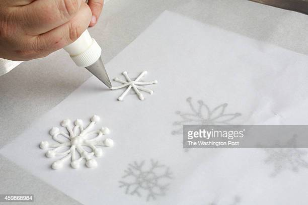 See the accompanying template for piping snowflake decorations Place the template under a sheet of parchment paper and trace with a firm white royal...