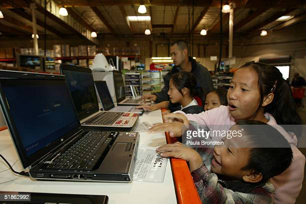 See Vang age 13 and her brother Pa Choua age 7 play with a laptop computer while the family went to buy groceries at Costco's warehouse supermarket...