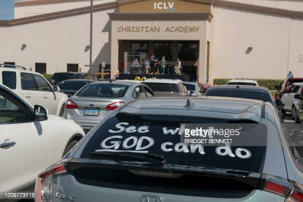 See what God can do is painted on a car as attendees gather for a drivein Easter service amid the Coronavirus pandemic at the International Church of...