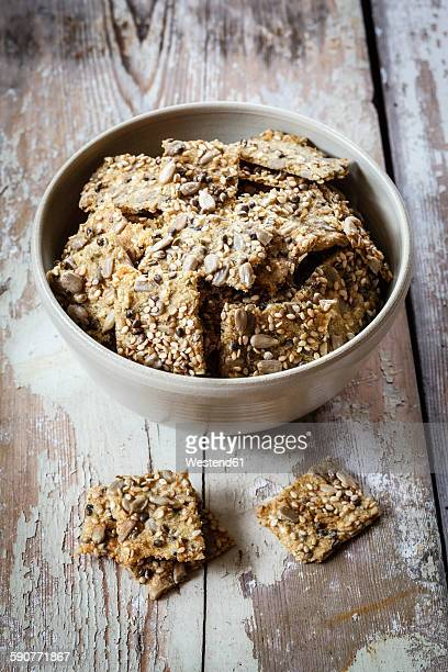 Seed crackers with hemp seeds in bowl, on wood