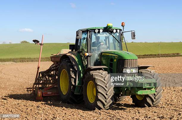 seed drilling, tractor planting crops - john deere tractor stock photos and pictures