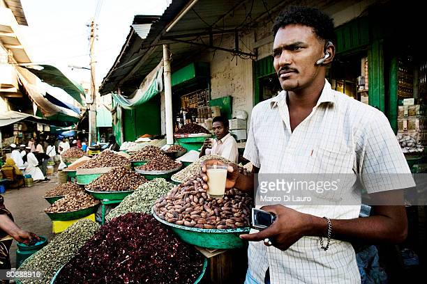 A seed trader is seen in front of his shop with a bluetooth auricular while he drinks a tea in the Omdurman Souq on January 11 2007 in Khartoum Sudan...