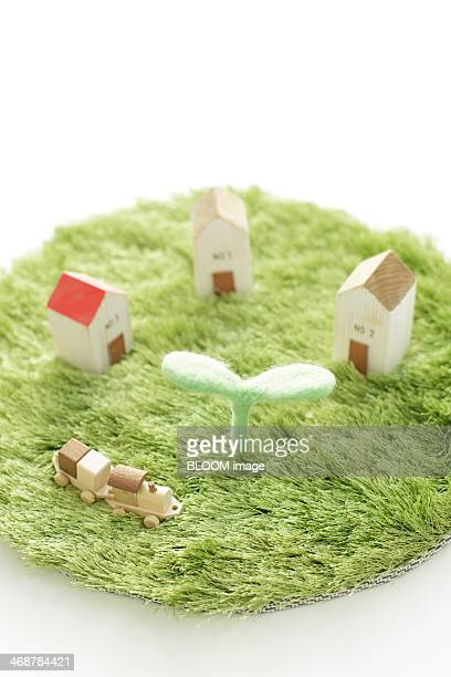 Seedling, model houses and toy locomotive on fake grass