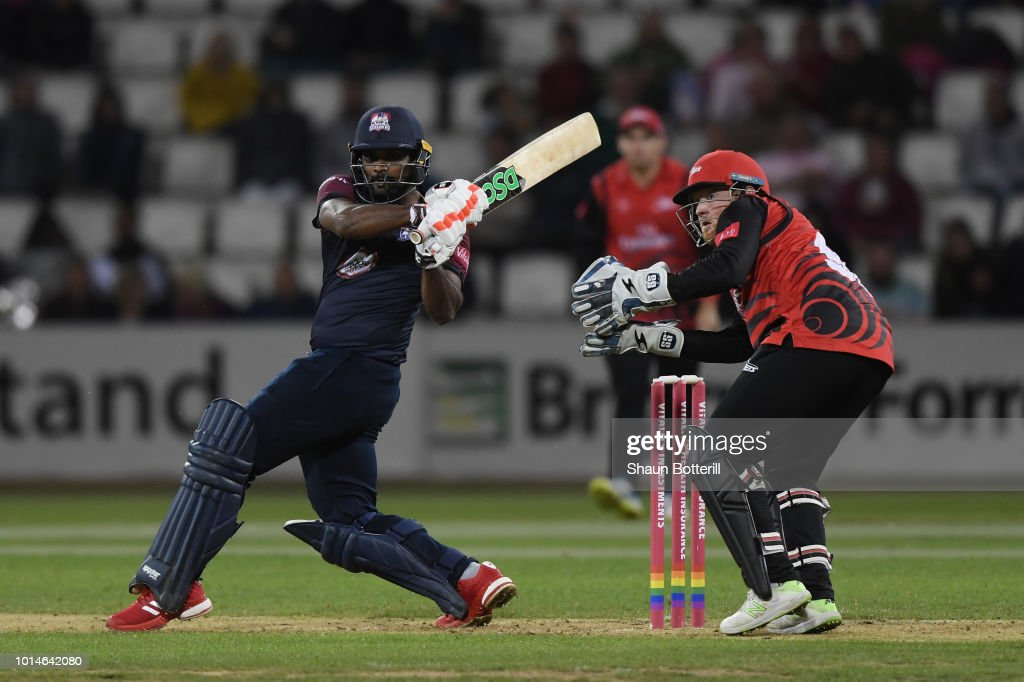 Seekkuge Prasanna of Northamptonshire Steelbacks plays a shot as Stuart Poynter of Durham Jets looks on during the Vitality Blast match between Northamptonshire Steelbacks and Durham Jets at The County Ground on August 10, 2018 in Northampton, England.
