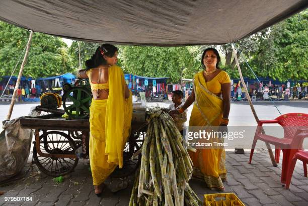 Seema and Pooja Meena from Jyotipura a village near Rajasthan's Kota have come to run a makeshift temporary sugarcane juice stall on May 17 2018 in...