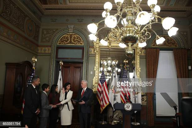Seema Verma participates in a swearingin ceremony officiated by US Vice President Mike Pence as her husband Sanjay daughter Maya and son Shaan look...