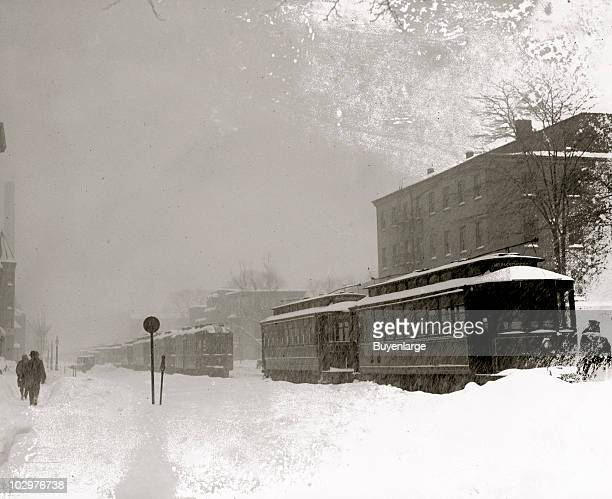 Seemingly empty trolley cars sit in the snow as pedestrians trudge past during the socalled Knickerbocker Storm a blizzard that dropped 28 inches of...
