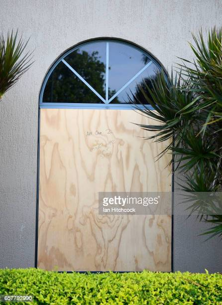 Seen are windows boarded up with plywood for protection at a funeral home as Townsville residents prepare for Cyclone Debbie on March 26 2017 in...