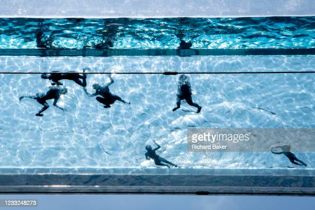 Seen from a ground perspective, swimmers enjoy the waters of the Sky Pool, a 25 metres-long transparent water pool bridging two 10-storey residential...