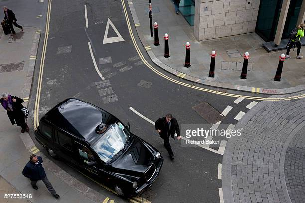 Seen from a high walkway above we see an aerial landscape of city road markings and roundabout junction As pedestrians walkby a licensed black taxi...