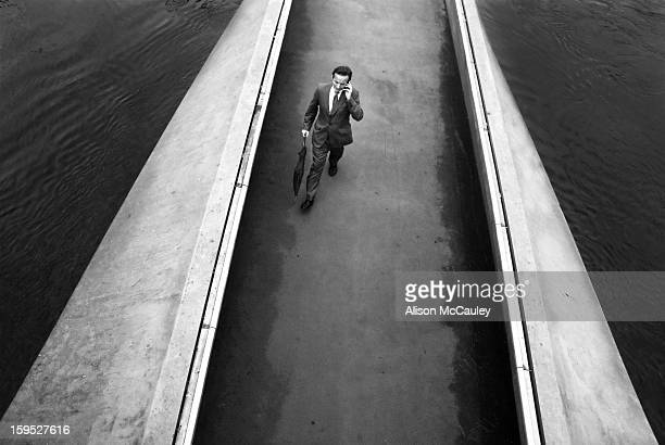 Seen from above, a businessman, talking on his phone and holding a closed umbrella in his other hand, strides across a bridge. On either side of the...