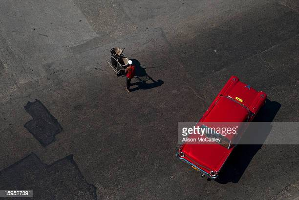CONTENT] Seen from above a road sweeper in a red top walks past a red classic old American car in Havana The surface of the road is an interesting...