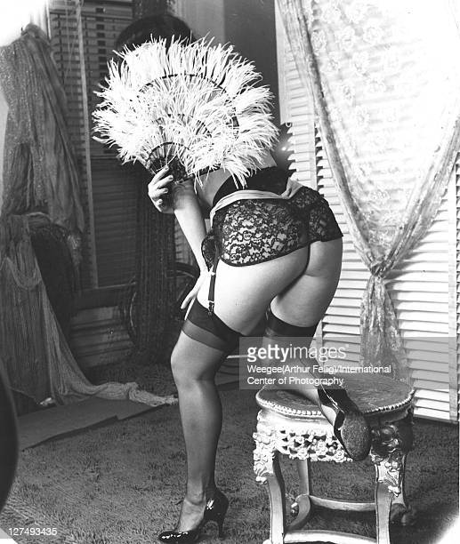 Seen from behind American pinup model Bettie Page poses in lingerie with a feather fan in front of her face mid 1950s Photo by Weegee/International...