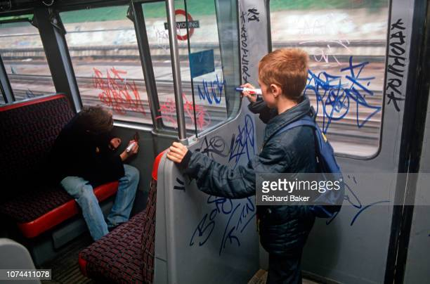 Seen from behind two young boys tag the inside the 1980s carriage of a 1990s London Underground train on 8th November 1989 in London England in 1980s...