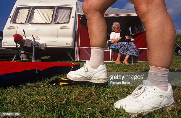 Seen from groundlevel a pair of feet in white trainers are seen large in the foreground on lush grass one standing on a foot pump as it inflates a...