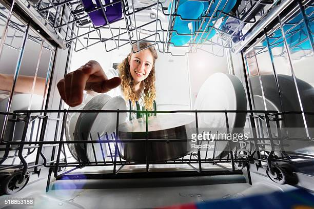 Seen from inside dishwasher, cute smiling girl loading or unloading