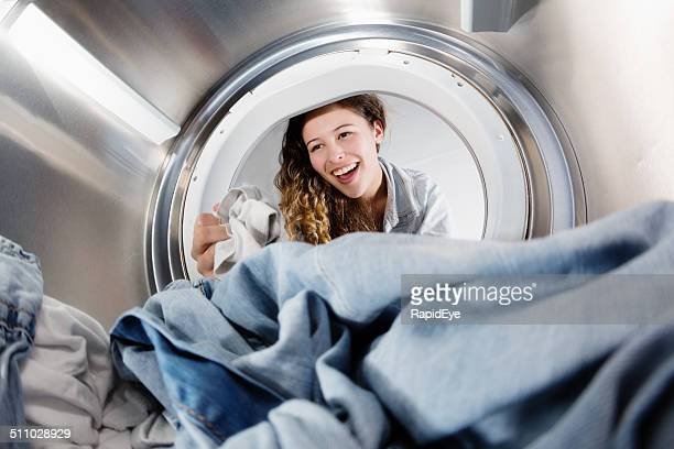 Seen from inside drum, pretty woman loading clothes dryer