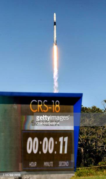 Seen from the Kennedy Space Center, the SpaceX Falcon 9 clears the launch pad -- with a countdown clock in the foreground -- from Cape Canaveral Air...