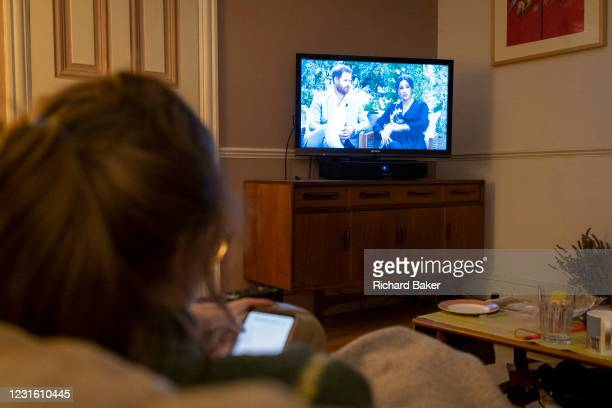 Seen from the rear, a young woman looks at the screen on her phone while watching the Duke and Duchess of Sussex's controversial TV interview with US...