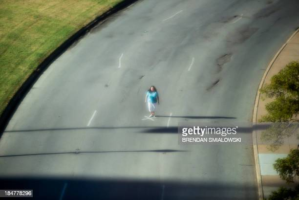 Seen from the sixth floor of the former Texas School Book Depository building a woman stands at an X which marks the approximate place where John F...