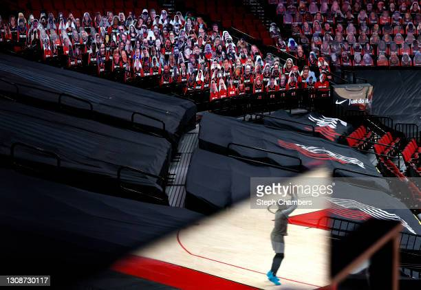 Seen in a plexiglass reflection, Damian Lillard of the Portland Trail Blazers warms up in front of cardboard cutouts of fans before the game against...