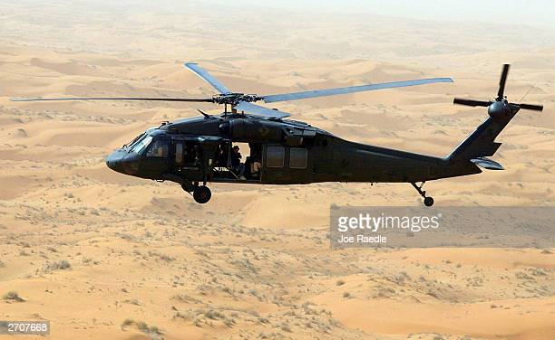 Seen in this file photo a Blackhawk helicopter from the 101st Airborne flies over the desert sands February 16 2002 during a reconnasance mission in...