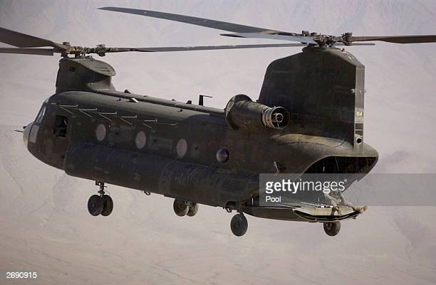 Seen in this file photo a tailgunner sits on the back ramp of a US Chinook 47 on a return trip to Kandahar during Operation Viper February 21 2003 in...