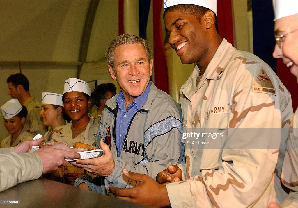 Seen in this handout photo provided by the U.S. Air Force, President George W. Bush delivers food during a surprise visit on Thanksgiving Day, November 27, 2003 in Baghdad, Iraq.