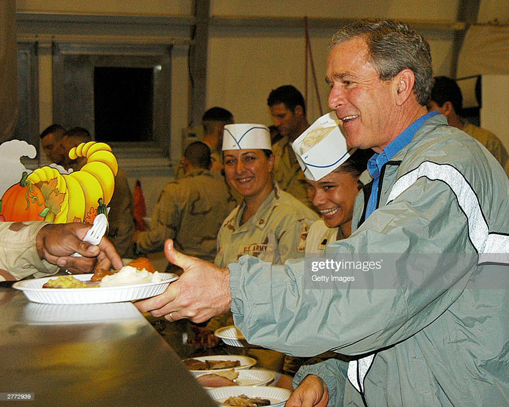Seen in this handout photo provided by the U.S. Army, President George W. Bush delivers food during a surprise visit on Thanksgiving Day, November 27, 2003 in Baghdad, Iraq.