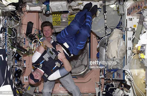 Seen in this undated ESA handout out photo European Space Agency astronaut Andre Kuipers performs an experiment while being assisted by his Russian...