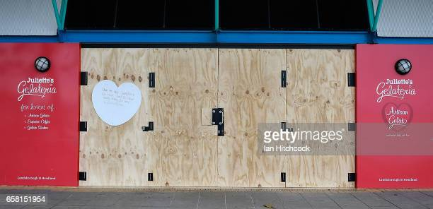 Seen is a shop closure notice and protective plywood panels at an ice cream shop on the Strand in preparation for Cyclone Debbie on March 27 2017 in...