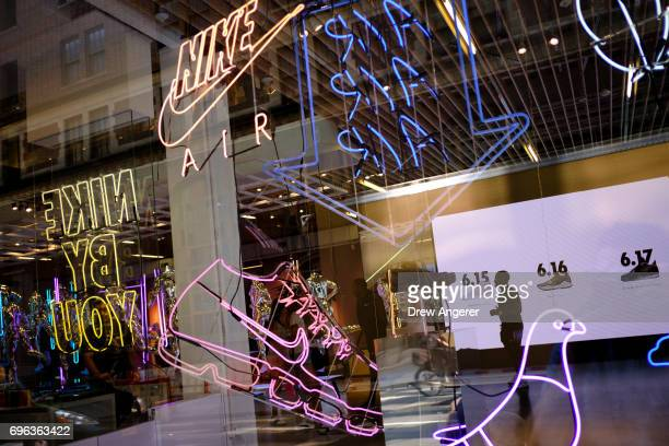 Seen through a store window a Nike employee stands in the entryway of the Nike SoHo store June 15 2017 in New York City Nike announced plans on...