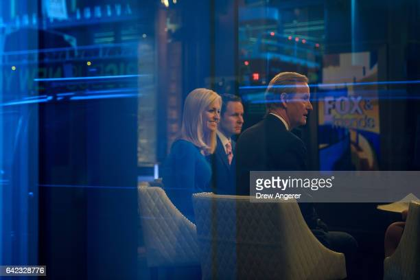 Seen through a window hosts Ainsley Earhardt Brian Kilmeade and Steve Doocy broadcast 'Fox And Friends' from the Fox News studios February 17 2017 in...