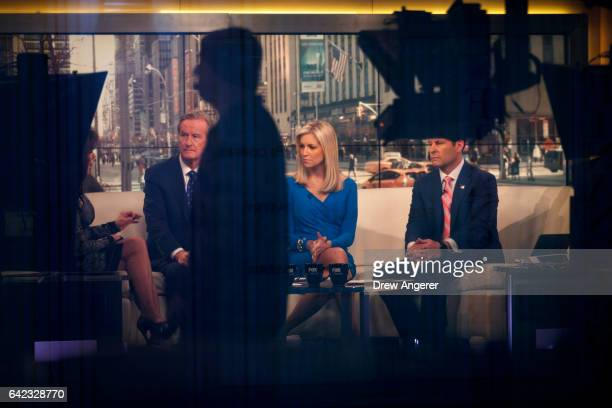 Seen through a window hosts Steve Doocy Ainsley Earhardt and Brian Kilmeade broadcast 'Fox And Friends' from the Fox News studios February 17 2017 in...