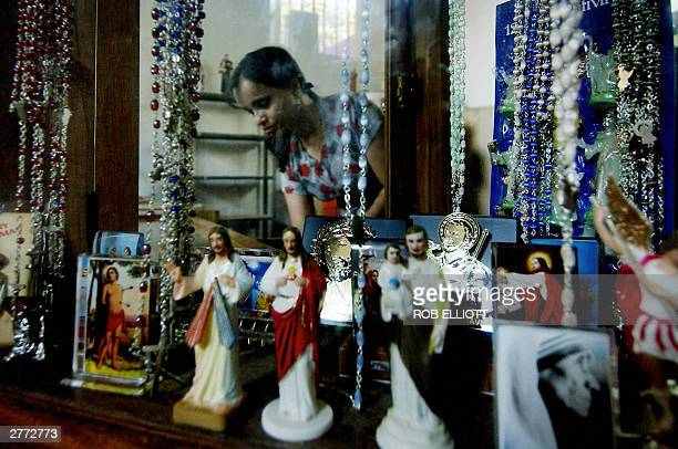 Seen through a wondow an Indian woman arranges a display with a statue of Saint Francis Xavier in the surroundings of the Saint Francis Xavier Church...
