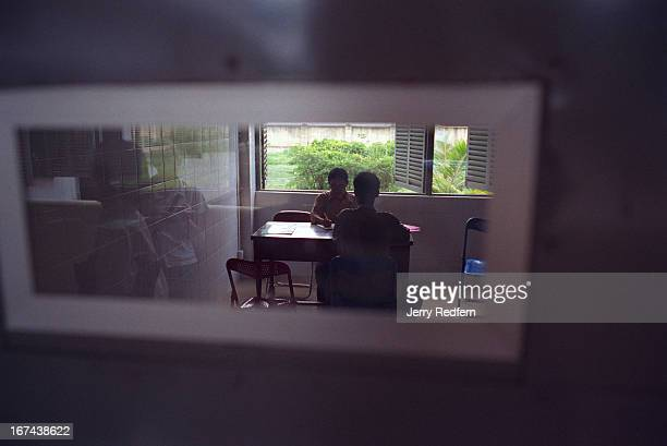 Seen through an examination room window psychiatrist Ang Sody talks with a patient in a new examination room at the Preah Norodom Sihanouk Hospital...