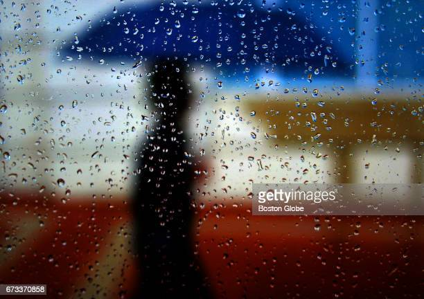 Seen through rainsoaked bus station shelter a pedestrian travels Commonwealth Avenue in Boston's Allston neighborhood in a heavy downpour during a...