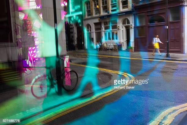 Seen through the abstract coloured mirrored glass of a backstreet bar a lady passerby dressed in a similar colour skirt to the doubleyellow lines...