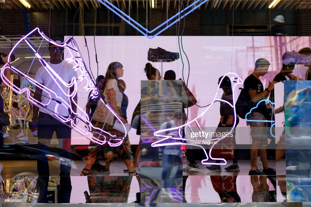 Seen through the store window, shoppers walk browse in Nike SoHo store,  June 15