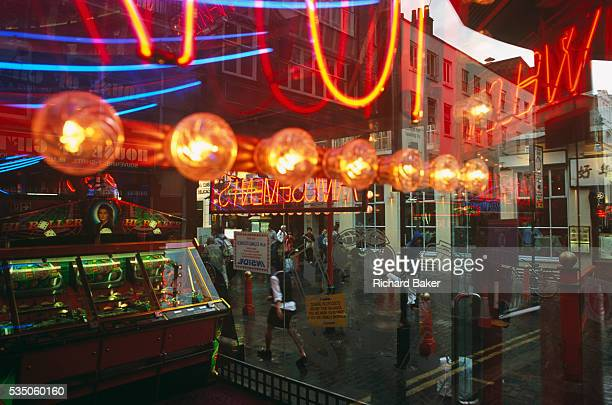 Seen through the window of an amusement arcade in London's Gerrard Street, Chinatown, we see the colourful neon lights that garishly shine from...