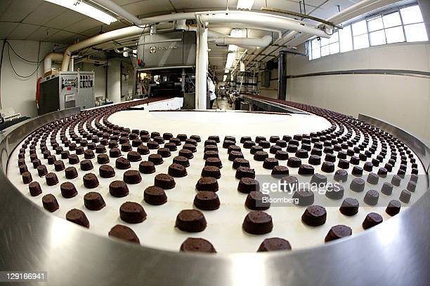 See's Candies Inc. Chocolate truffles travel on a conveyor belt before being coated in the truffle room at the company's factory in San Francisco,...